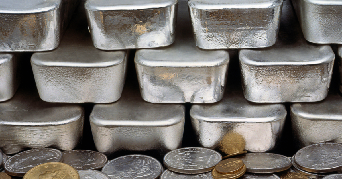 A stack of silver bullion bars atop a pile of gold and silver coins.